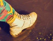 Bein in den Kampfstiefeln kommt auf das dünne Eis Stockfotografie