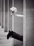 Bein der Braut und des Bräutigams mit einem Blumenstrauß der Hand Stockfotografie