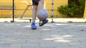 Beinarbeit eines Jungen mit einem Ball auf einer Straßenfußballneigung stock video