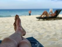 Beine auf einem beachchair und einem undeutlichen Mann, die ein Buch auf dem Strand lesen Stockfotos