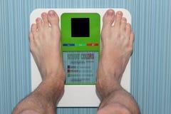 Beine bemannen auf elektronischen Skalen des Bodens Stockbilder