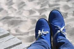 Beine in den blauen Velourslederschuhen auf dem Sand Lizenzfreie Stockbilder