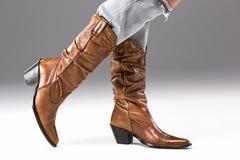 Beine in den Jeans und in den Cowboystiefeln Lizenzfreie Stockbilder