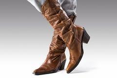 Beine in den Jeans und in den Cowboystiefeln Lizenzfreies Stockfoto