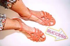 Beine in den rosa Sandalen, die an zum Erfolg gehen Lizenzfreies Stockfoto