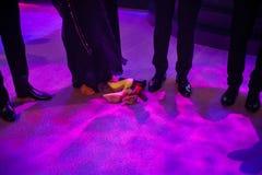 Beine in den Schuhen, barfuß und in den Schuhen an einem Hochzeitsfest Stockfotografie