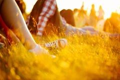 Beine in den Sportschuhen oder -turnschuhen im Gras Sommer-Lebensstil Buntes warmes gelbes Tonen Leute am Feiertag, der auf dem B Stockbild