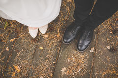 Beine der Braut und des Bräutigams: schwarze Schuhe, Weiß folgten Schuhen, Details eines Hochzeitskleides auf den Fersen Stockfotografie
