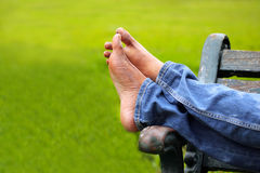 Beine der entspannenden erwachsenen Person auf einer Parkbank Stockfoto