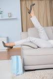 Beine der Frau mit den Fersen, die auf Couch liegen Lizenzfreie Stockfotografie