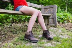 Beine der Frau sitzend auf Bank im Wald Lizenzfreie Stockbilder