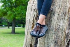 Beine der jungen Frau sitzend auf Baumstamm Lizenzfreie Stockfotografie