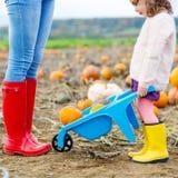 Beine der jungen Frau und ihres kleines Mädchen daugher in den rainboots Lizenzfreie Stockfotografie