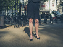 Beine der jungen Geschäftsfrau im Park Lizenzfreies Stockfoto