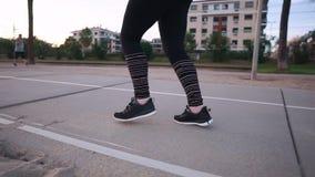 Beine der laufenden Frau bewegend über Weg des Stadtparks in der Sonnenuntergangzeit stock video