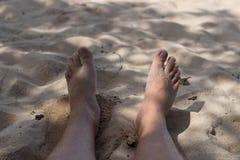 Beine der Person auf einem Sand Beine eines Mannes auf dem Sandion der Strand von oben Horizontaler Freienschuß Bali-Insel Lizenzfreie Stockfotos
