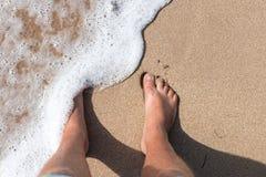 Beine der Person auf einem Sand Beine eines Mannes, der auf dem Sandion den Strand von oben steht Horizontaler Freienschuß bali Lizenzfreie Stockbilder