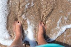 Beine der Person auf einem Sand Beine eines Mannes, der auf dem Sandion den Strand von oben steht Horizontaler Freienschuß bali Lizenzfreies Stockbild
