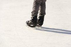 Beine des Eisschlittschuhläufers auf Eisbahn lizenzfreies stockbild