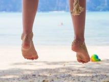 Beine des jungen Mädchens auf dem Strand Lizenzfreie Stockfotos
