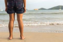 Beine des Kinderstands auf dem Strand Lizenzfreie Stockfotografie