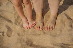 Beine des Kindes auf dem Sand Stockfoto