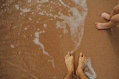 Beine des Kindes auf dem Sandstrand Stockbilder