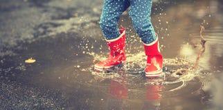 Beine des Kindes in den roten Gummistiefeln, die in Herbst springen, macht matschig Lizenzfreies Stockfoto