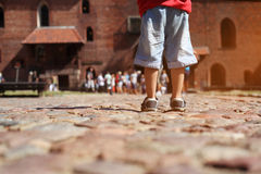 Beine des Kleinkindjungen auf der Steinstraße auf der Exkursion Lizenzfreies Stockfoto