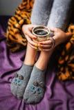Beine des Mädchens in den warmen woolen Socken und in einer Tasse Kaffee-Erwärmung lizenzfreie stockfotos