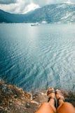 Beine des Mädchens sitzend auf Rand der Klippe und der schönen Ansicht von Meer, Bergen und weißem Boot/Yacht, Montenegro stockfotos