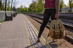 Beine des Mädchenwartezugs mit backback Stockfotos