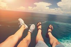 Beine des Mannes in den Sandalen und in der Frau in den Sportschuhen, die über blauem Ozean sitzen stockfoto