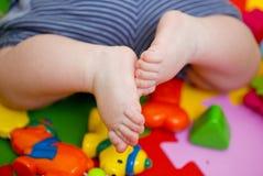 Beine des neugeborenen Babys unter bunten Spielwaren Lizenzfreie Stockbilder
