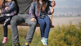 Beine des Vatis schwingend mit Töchtern auf einem Schwingen unter einem Baum Nahaufnahme stock footage