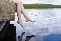 Beine, die über Wasser baumeln stockfoto