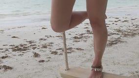 Beine, die auf hölzernem Schwingen auf Strand schwingen stock video