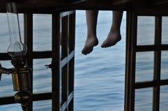 Beine, die von der Plattform baumeln Seeansicht durch das offene Fenster lizenzfreie stockfotografie