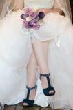 Beine einer Braut mit Blumenstrauß und blauen Schuhen Lizenzfreies Stockfoto