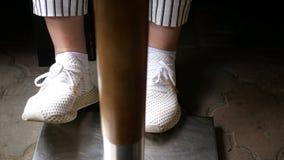 Beine einer Frau in den weißen Turnschuhen und in den gestreiften Schwarzweiss-Hosen stampfen unter der Tabelle stock video