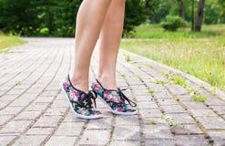 Beine einer Frau, die auf den Bürgersteig geht Lizenzfreies Stockfoto