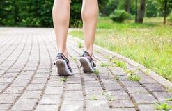 Beine einer Frau, die auf den Bürgersteig geht Lizenzfreies Stockbild