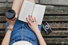 Beine einer jungen Frau in der kurzen Jeanshose, auf einer Bank Lizenzfreies Stockbild