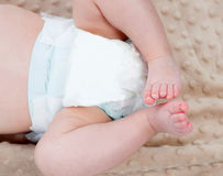 Beine eines Babys mit Windel Stockbild