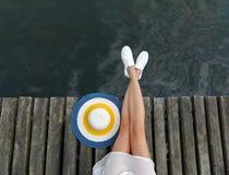 Beine eines kaukasischen Mädchens auf dem Strand mit einer Strandhutnahaufnahme Stockbild