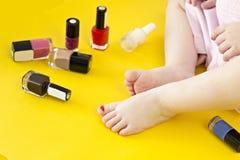 Beine eines kleinen Mädchens und der Kosmetik auf einem gelben Hintergrundbaby lizenzfreie stockfotos