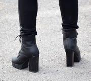Beine eines Mädchens in den schwarzen Fersen Stockfotos
