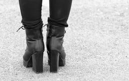 Beine eines Mädchens in den schwarzen Fersen Stockfotografie