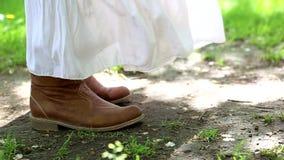 Beine eines Mädchens in einem weißen Kleid und in den Schuhen stock video footage