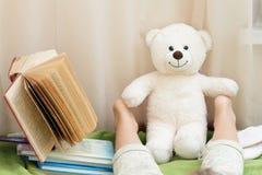Beine eines Mädchens mit dem Buch Stockfotos